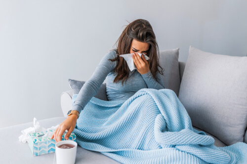 Sick woman with seasonal allergy lying in bed.