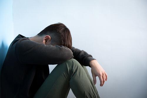 The depressed man sit on the floor