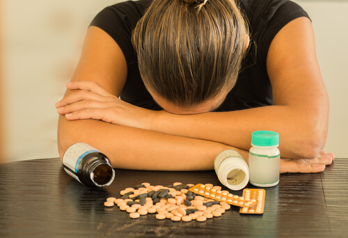 Woman lying on wooden table with Benadryl tablets and pills