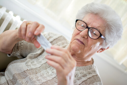 senior woman with glasses reading Benadyl label
