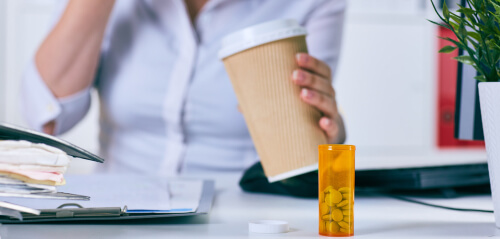 businesswoman holding cup of coffee and benadryl pills
