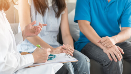 Patient couple consulting with doctor about rehab program