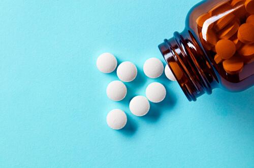 White medical pills and tablets spilling out of a drug bottle.