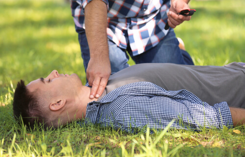 Passerby calling ambulance while checking pulse of unconscious man outdoors