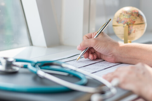doctor writing on medical health care record