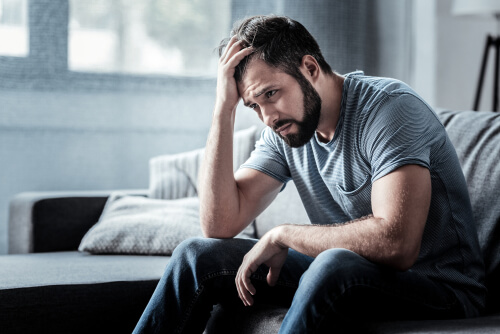 man experiencing flakka withdrawal sitting on the sofa and holding his forehead