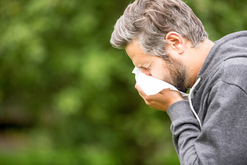 man with allergic sneezing