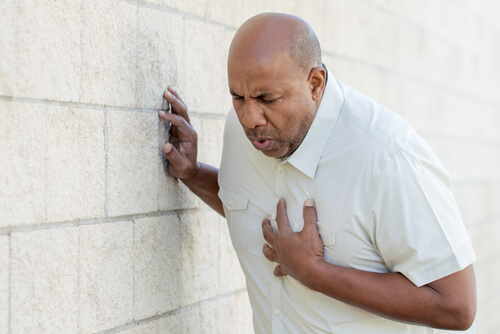 man holding his chest with heart problems