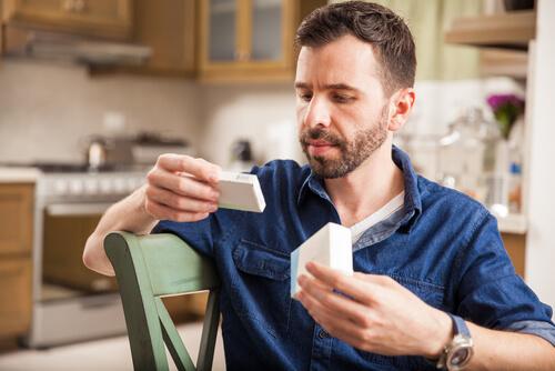 man reading a prescription on pills