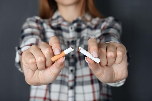 woman breaking cigarette in hands