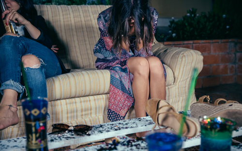 woman holding her head sitting in the sofa in a party