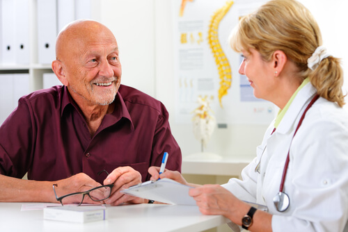 Doctor talking to her male senior patient