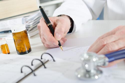 Male medicine doctor hand hold pills and write prescription