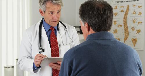 Patient asking elderly doctor