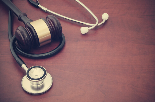 Wooden gavel and stethoscope on the table