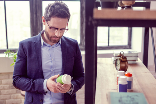 man looking at the bottle with pills