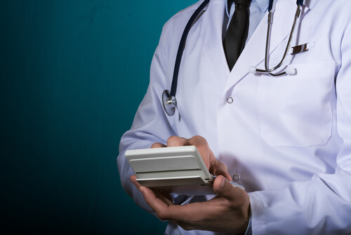 doctor in a white coat holds a calculator