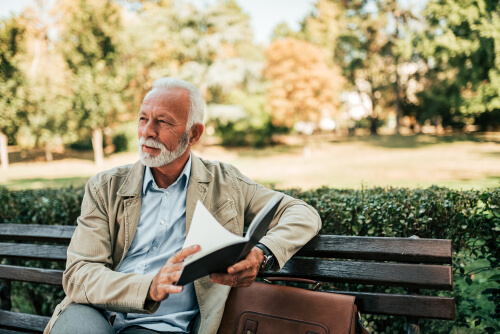 mature man reading book outdoors