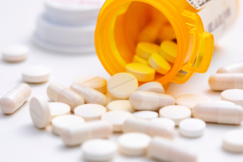 prescription opioids spilling from orange bottle