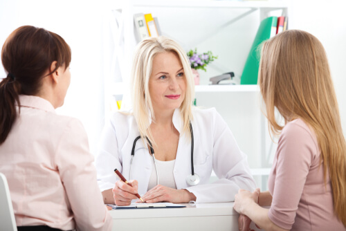 mother and daughter talking to a doctor