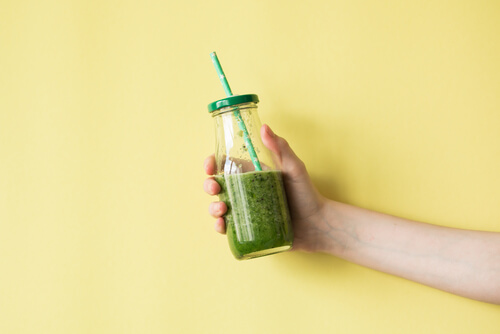 woman holding a green smoothie