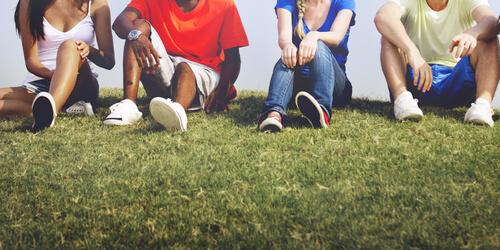 group of teens sitting together on the grass