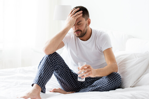 sad man drinking water in bed