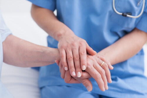 nurse holding the hand of the patient