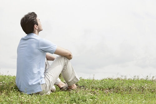 relaxed man sitting on grass
