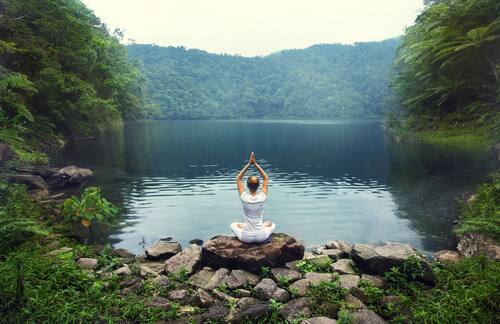 woman practicing yoga near the lake