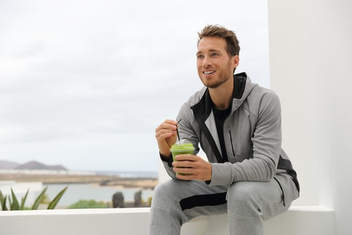 Healthy man drinking green smoothie
