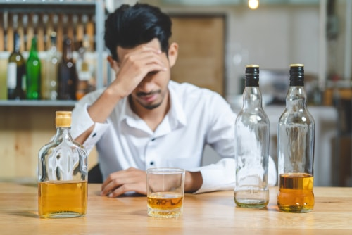 Young relapsed man drinking alcohol