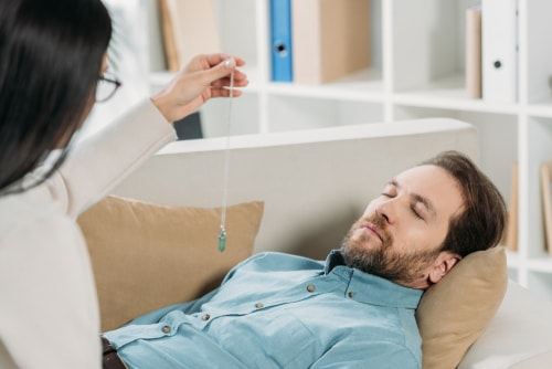 holistic therapist hypnotising bearded man
