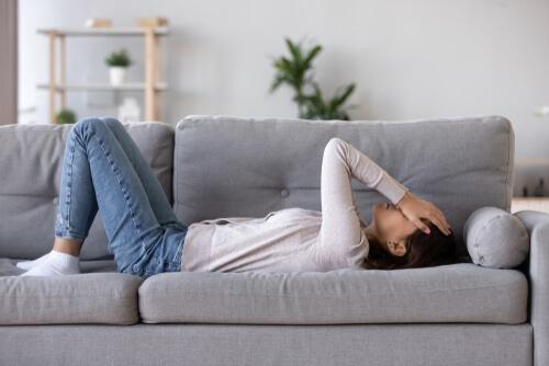 sad woman lying on sofa