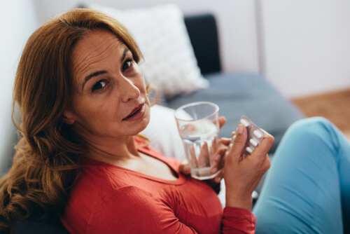 middle-aged woman taking pills