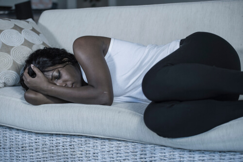 woman feeling sick lying on a couch