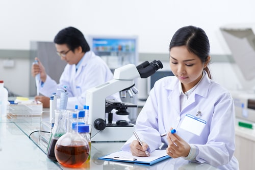 Laboratory assistant filling medical report.
