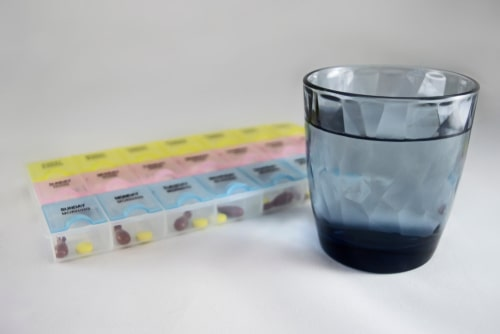 Pill box and a glass of water.