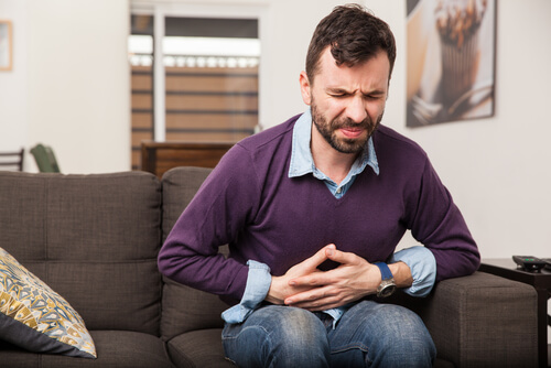 man with stomach ache on a sofa