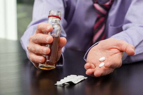 man taking pills with alcohol