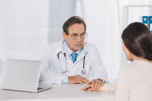 Senior doctor consults female patient