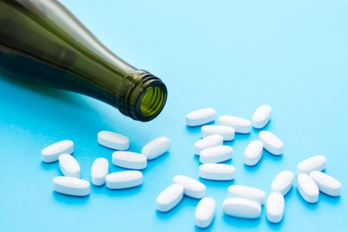oval pills an empty wine bottle