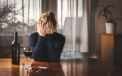 Depressed woman is drinking red wine and taking pills.