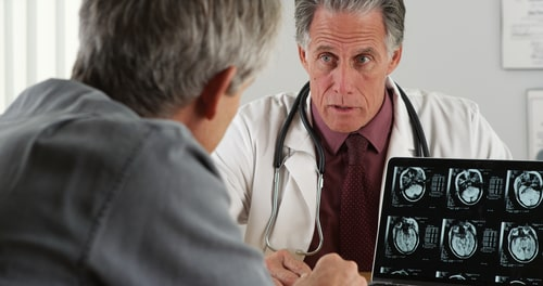 Doctor discussing elderly patient's mri scans.