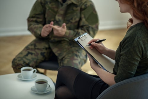 Therapist taking notes of PTSD patient.