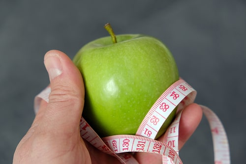 Green apple and tape measure.
