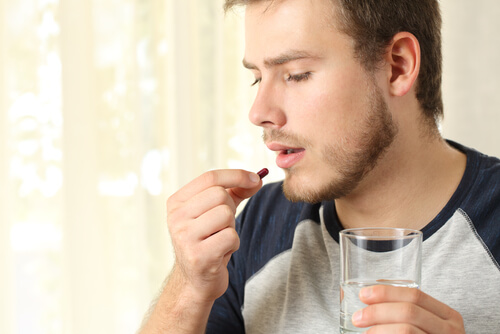 young man taking a capsule