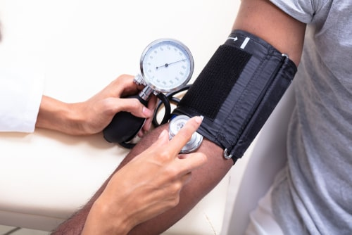 Checking old man patient arterial blood pressure.