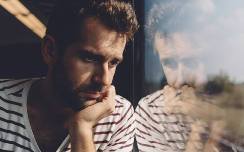 depressed man near the window