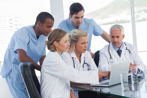 medical specialists using a laptop.